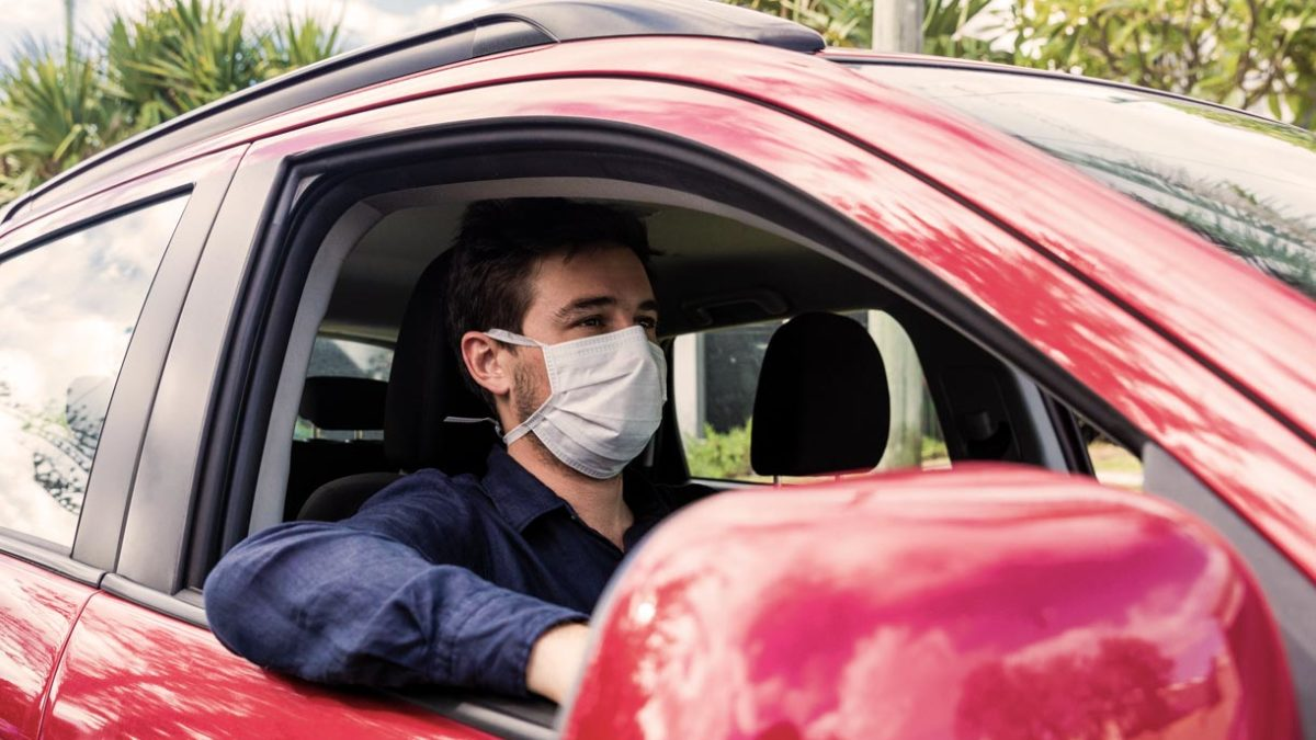 Article image of man wearing mask while driving