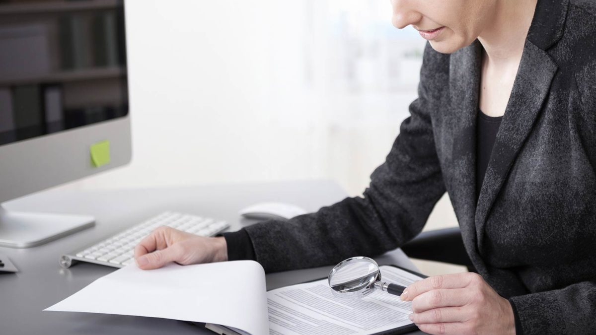 Article image of woman analyzing a document